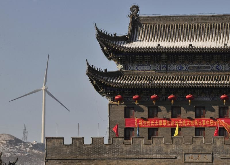 a-wind-turbine-is-seen-near-a-gate-of-the-ancient-city-of-wushu-in-diaobingshan-liaoning-province-january-18-2011